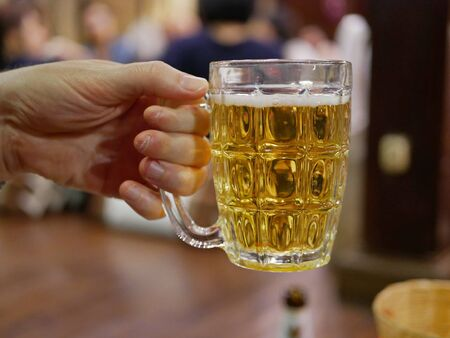Close up of golden bubbling beer in a cup holding by one hand ready to drink it up with blurry background of people at a party