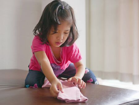 Little Asian baby girl learning to fold her own pants - children help doing household chores