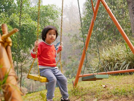 Little Asian baby girl enjoys riding a swing at a playground Stock Photo