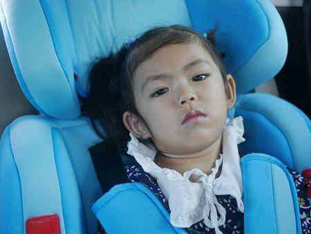 Kleines Baby, 30 Monate alt, das sich im Autositz langweilt und darauf wartet, auf einer Reise an einem Ziel anzukommen - Babyentwicklung, indem man lernt, geduldig zu warten