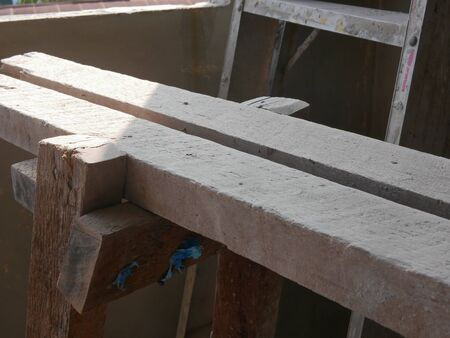 A dusty grungy wooden stand for a construction worker to stand on for concrete wall plastering and paintingl