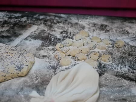 Pieces of massaged dough mixed with black sesame seeds on a table getting ready to be deep fried to make Chinese bread or Pa Tong Go Imagens