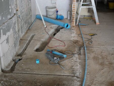 Construction site where the concrete floor in the house being digged out for laying a sewer pipe for toilet