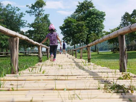Asian baby girl walking to her mother and younger sister who were standing and waiting for her on a bamboo wooden pavement - family means no one gets left behind or forgotten