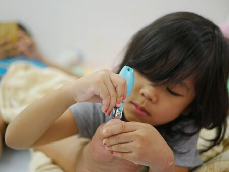 Little Asian baby girl, 46 months old, learning to cut her mother's toenails, while her mom was using a smartphone on a bed at home Imagens