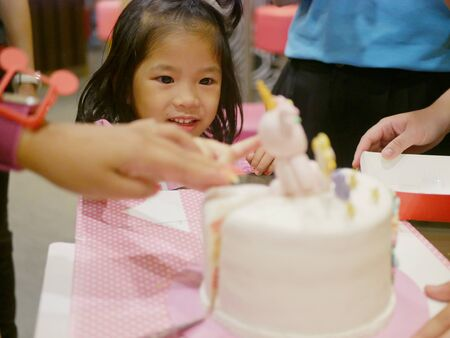 Little baby girl reaching her hand out to a birthday cake in front of her, as it is so irresistibly attracted to her