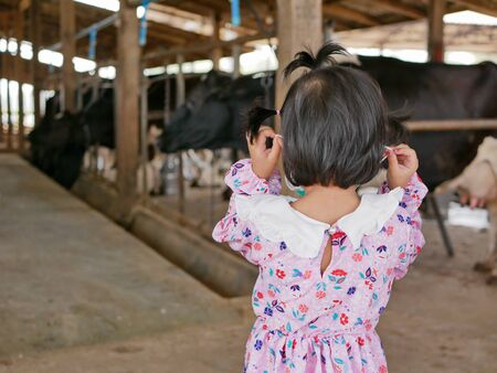Little baby girl visiting an organic dairy farm - tour with a kid learning how far does their milk travel to get to her cup