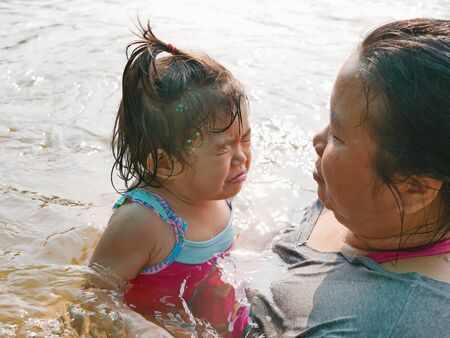 Little Asian baby girl, 25 months old, sneezing while playing water in a river with her auntie