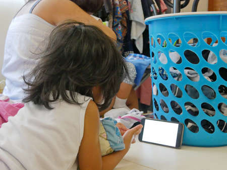 A little baby girl watching a smartphone leaning onto a basket filled with clothes needed to be ironed by her mother - it is  tempting to hand a phone to children to calm them while doing house chores Stock fotó