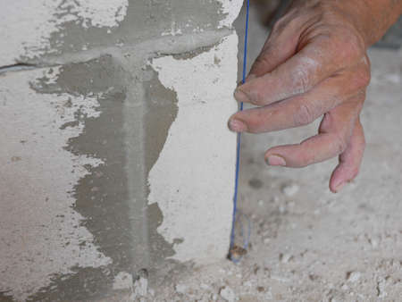 A man's hand holding on a blue string, established by the use of a plumb bob or plummet, used as a vertical reference line for wall in construction