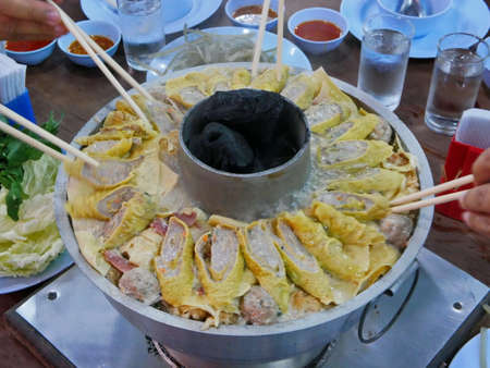 Big cooking hot pot with hot charcoals in the middle, originally from Yunnan, China, adapted and cooked tastier in the North of Thailand. The menu is so called Suki Yunan 免版税图像