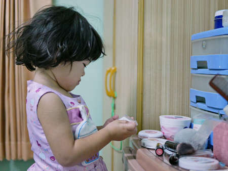 Little baby girl, 2 years old, enjoys putting on / using her mom's cosmetics - child playing make up