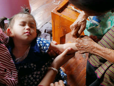 A Thai baby girl falling asleep, while her great grandmother doing a blessing for her by waving a white string ( Sai Sin ) around her hand - Thai traditional blessing from an elder one