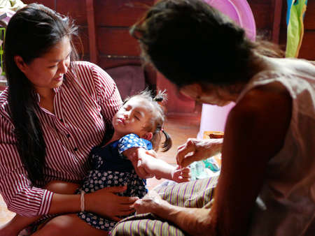 Thai mother carrying her baby girl, while allowing her grandmother to do a blessing for the toddler by waving a white string ( Sai Sin ) around child's hand - Thai traditional blessing from elder one 免版税图像