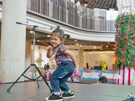 Little baby girl, 2 years old, enjoys dancing on a setting-up consert stage at a public space - children needs space of expression and exploration of movement
