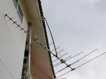 A broken television anttenna collapsing, hanging and almost dropping down from the house's roof