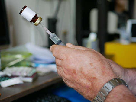 An old man's hands carefully pulling the medicine into the syringe by himself at home - self injecting in the elderly 免版税图像