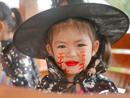 Little girl, 3 years old, is happy with her Halloween makeup, stitches, wound, on her face done by herself before attending her school event