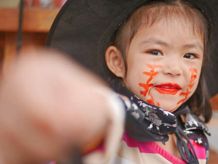 Little girl, 3 years old, is happy with her Halloween makeup and pretend playing as a powerful witch 免版税图像