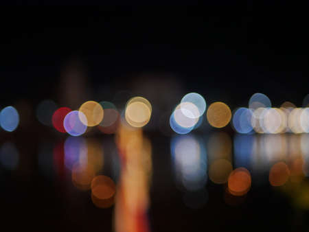 Bokeh of colorful lights on the bank of a river and their reflection, during night time