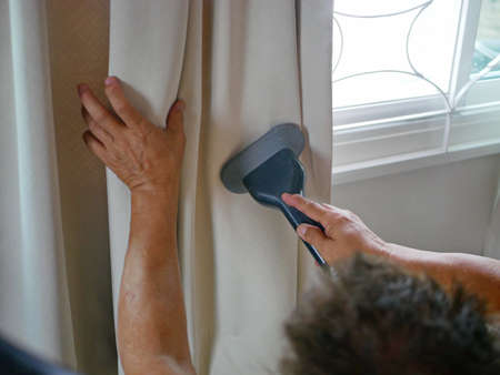 Hands of a man using a clothes / garment steamer providing service on steam cleaning curtains in a house