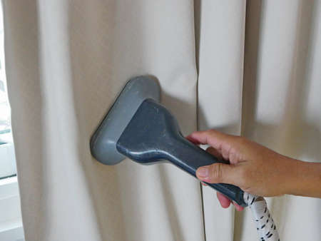 A hand of a man holding on a clothes / garment steam head while doing a steam clean for house curtains