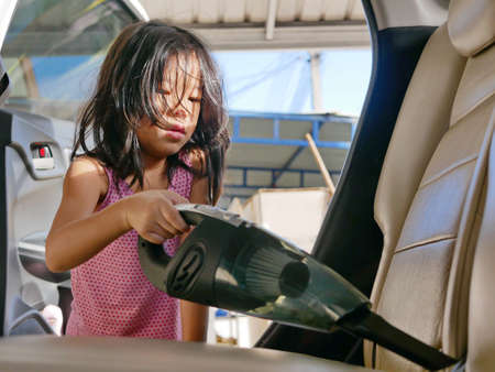 Little girl, 4 years old, cleaning a car using a portable handheld vacuum cleaner - encourage your child development by allowing them to help doing house chores Archivio Fotografico
