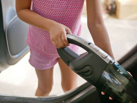 Little girl's hands using a portable handheld vacuum cleaner to clean up a car - encourage your child development by allowing them to help doing house chores 免版税图像
