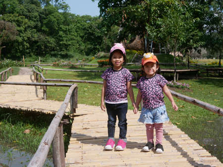 Little Asian baby girls, sisters, 3 and 2 years old, smiling and making cute pose together for outdoor photo shoot