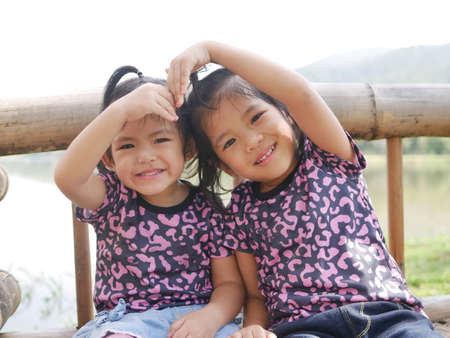 Two little girls, sisters, 2 and 3 years old, smiling and making a heart shape arms together on a bench in the evening sunlight - sisters bond, love, and friendship 免版税图像