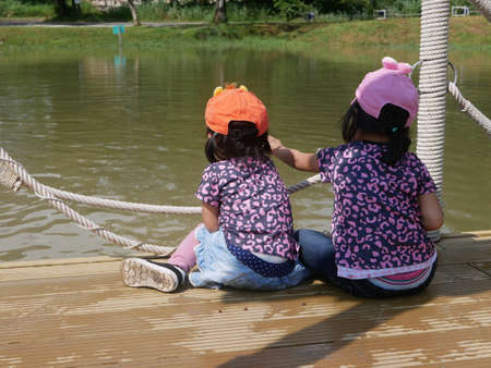 Two little baby girls, sisters, sit together and enjoy feeding fishes in the water with dry pallet food 免版税图像