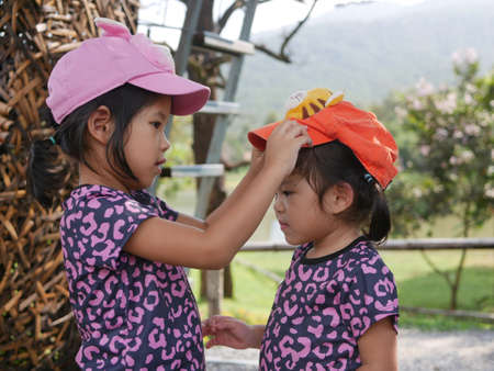 Little older sister, 3 years old, putting on her younger sister, 2 years old, a cap - sisters love / care / bond 免版税图像