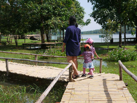 A mother walking on a bamboo wooden pavement along with her two little baby girls - spending time outdoor with your children 免版税图像