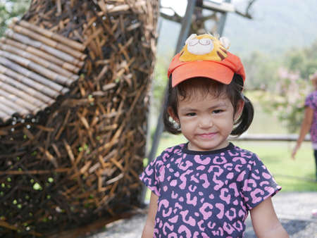 Little Asian baby girl, 2 years old, enjoys taking photograph outdoor during a trip with her family