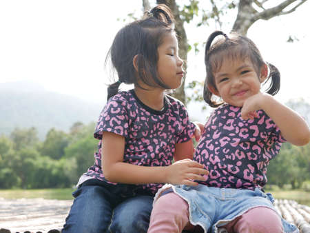 Two little girls, sisters, 3 and 2 years old, kissing on a bamboo bench in the evening sunlight - sisters bond, love, and friendship