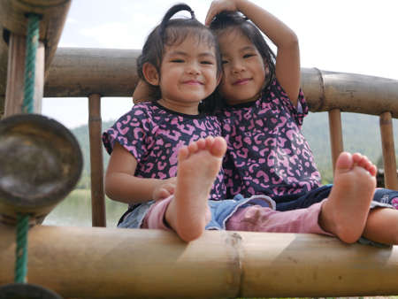 Two little girls, sisters, 2 and 3 years old, smiling and making a heart shape on a bamboo bench near a lake - sisters bond, love, and friendship
