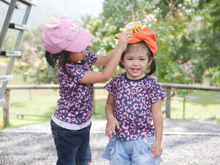 Little older sister, 3 years old, putting on her lovely younger sister, 2 years old, a cap - sisters love / care / bond