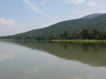 Green hill, blue sky, white clouds, and a reservoir with reflection in the water - relaxing landscape