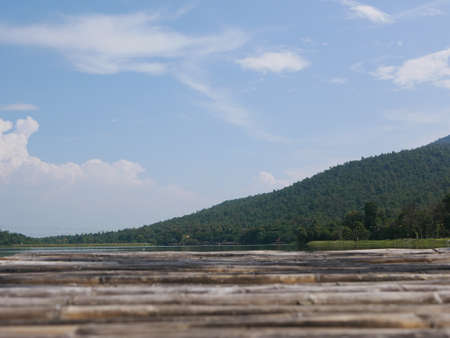 Green hill, blue sky, white clouds, and a reservoir with a defocus bamboo wooden terrace - relaxing landscape