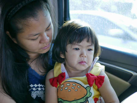 Little baby girl feeling sad, upset, depressed in a car with the mother being by her side - providing a child an emotional support