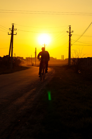 man on bike goes on the road during the sunset