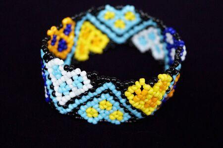 female color beaded bracelet handmade on a black background isolate