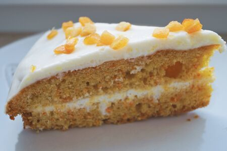 Eating dessert sweets are a carrot cake with a white creamy cream and candied fruits on a white plate