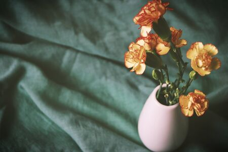 bouquet of orange and yellow carnation flowers on a background of green cloth tablecloth romantic plot seasonal nature detail summer spring Banque d'images