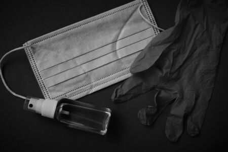Medical mask for face, disinfection tool in a vial and gloves against viruses in the epidemic black and white photo