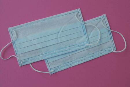 Two white medical masks for face on the pink