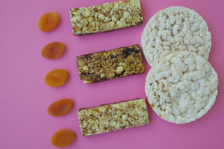 Three bars with muesli and dried apricots on a background of pink paper healthy food breakfast macro photo isolates Banque d'images