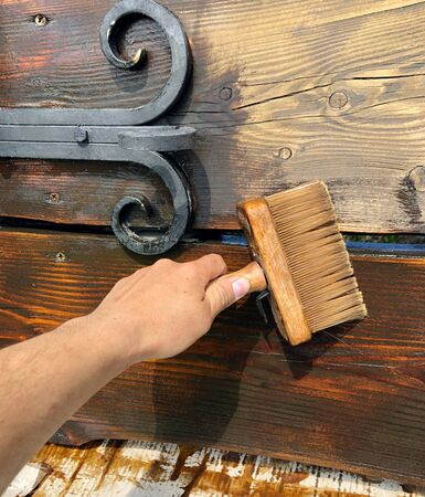 the hand of man with a brush paints lacquer wooden bench reconstruction works