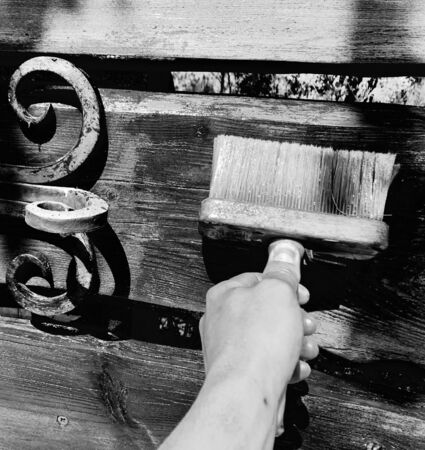 man with brush in hand lacquer Board old vintage wooden bench repairs at home black and white retro photo Banque d'images