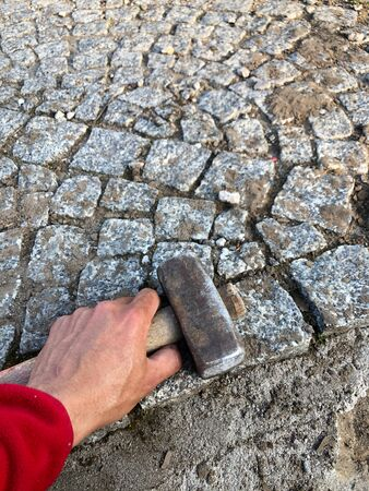 the hammer in the man's hand on a background of gray paving stones construction tools for physical work macro photo
